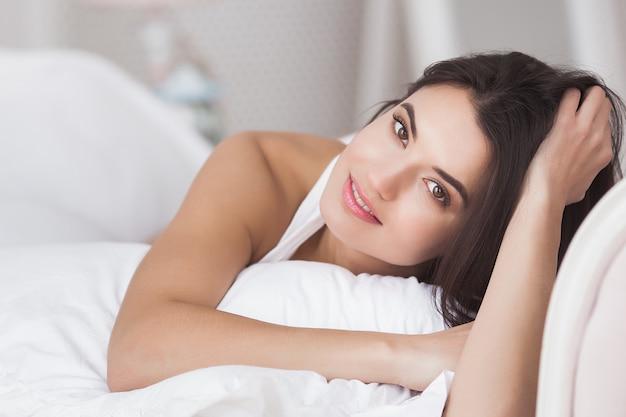 Очень красивая женщина в постели. портрет молодой привлекательной леди в спальне Premium Фотографии