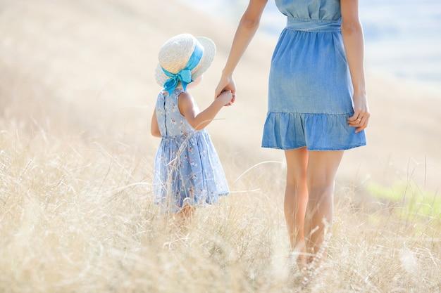 若い可愛い母と娘の屋外。野生の自然フィールドに幸せな家族のクローズアップの肖像画。楽しんでいる女の子。 Premium写真