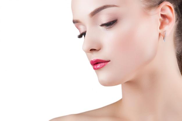 美しさの肖像画。若い美しいブロンドの女性。白の魅力的な女性。女性が化粧をする Premium写真
