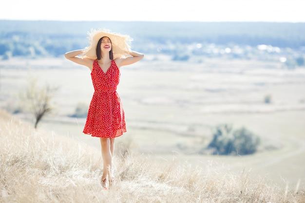 Молодая красивая женщина портрет на открытом воздухе на сочное лето или осень женщина на время падения. леди на природе носить красное стильное платье. Premium Фотографии