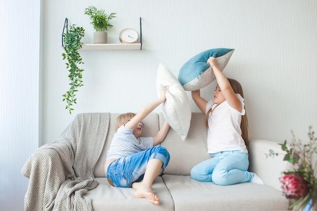 屋内で楽しんでいる小さな子供たち。ソファで遊ぶ子供たち。枕投げ。兄と妹が家で混乱しています。 Premium写真