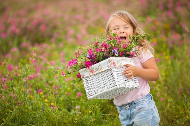 笑顔と花でいっぱいのバスケットで叫んで非常にかわいい感情的な女の子。うれしそうな子 Premium写真
