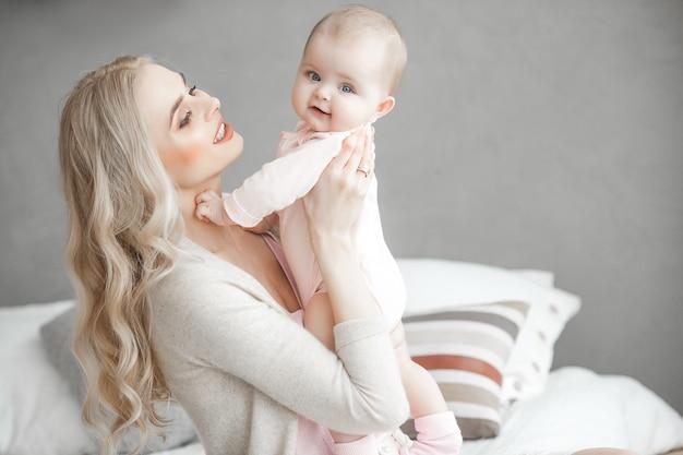 Молодая мать, забота о ее маленькая девочка. красивая мама и ее дочь в помещении в спальне. любящая семья. привлекательная мама с ребенком на руках. Premium Фотографии
