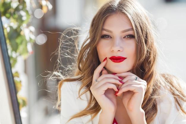 屋外の魅力的な若い女の子の肖像画。カメラを見て美しい都市の女性。赤い唇を持つ女性。 Premium写真