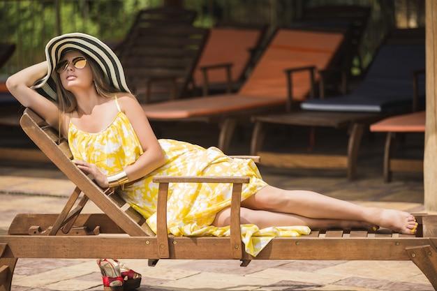 ラウンジャーで屋外でリラックスした女性。帽子の女性。夏の若い女性。黄色のドレスを着ている女性。 Premium写真