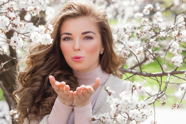 花と春の背景に若い魅力的な女性。美しい少女の肖像画を閉じます。屋外の庭の女性 Premium写真
