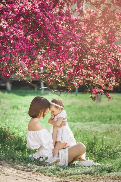 彼女の小さな女の赤ちゃんを持つ若い美しい母親の肖像画。愛する家族の静止画をクローズアップしてください。ピンクの花で彼女の子供を押しながら笑顔の魅力的な女性。 Premium写真