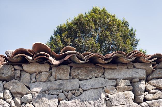 アンティークドライ石積みの石の壁と屋根の粘土タイルの詳細 Premium写真