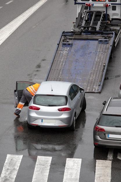 フラットベッドレッカー車のプラットフォームにロードする準備ができている都市通りの道路で壊れた車のシーン Premium写真