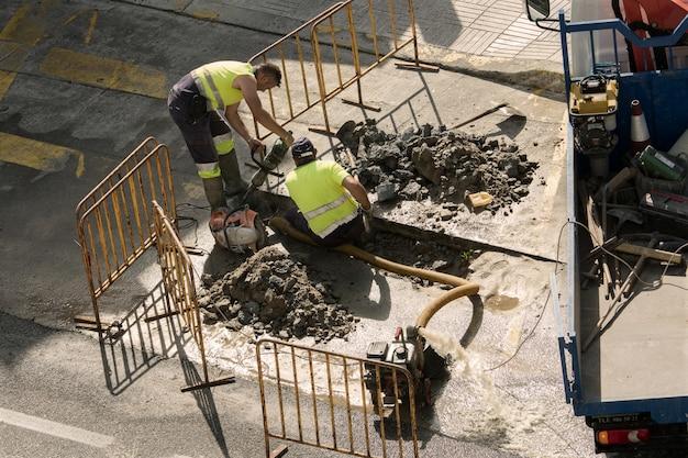 道路上の壊れた水道管を修理する労働者 Premium写真