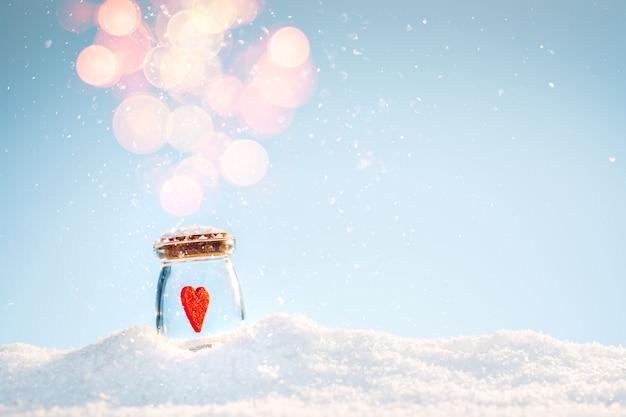 Красный чувствовал светящееся сердце в банке на снегу в зимний солнечный день. день святого валентина Premium Фотографии