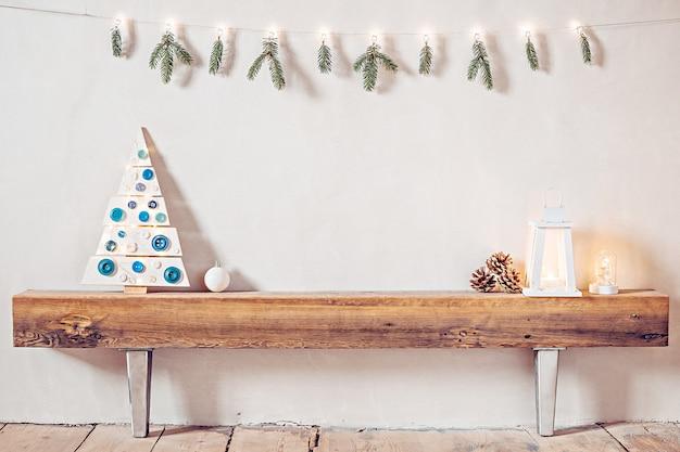 Уютная деревенская композиция в деревенском доме с елкой и фонарем на старом деревянном бревне Premium Фотографии