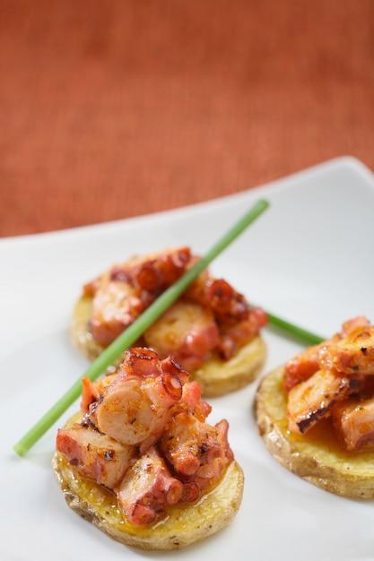 タコとジャガイモの前菜、お祝いのケータリングのプレゼンテーション。 Premium写真