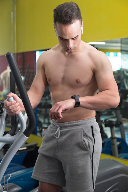 楕円形のマシンで時計を見て筋肉の若い男。 Premium写真