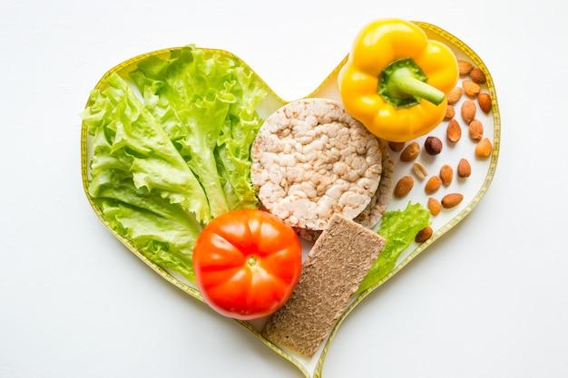Сердце из рулетки с овощами орехи и фрукты концепции диеты Premium Фотографии