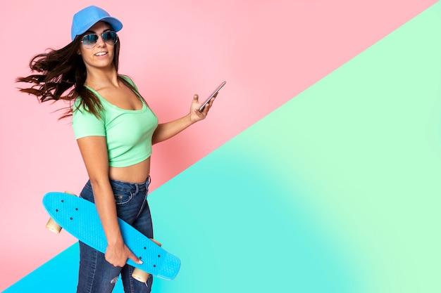スケートボードと携帯電話を保持しているファッションのスタイルで頭に帽子の黒い髪の少女 Premium写真