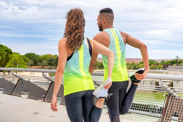Пара спортсменов в образе белой женщины негритянка выполняет упражнения на растяжку на ногах Premium Фотографии