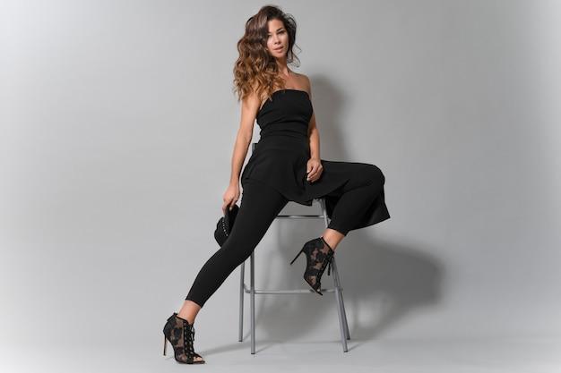 Портрет красивой женщины брюнетка с красивой улыбкой, одетые в черные одежды сидя Premium Фотографии