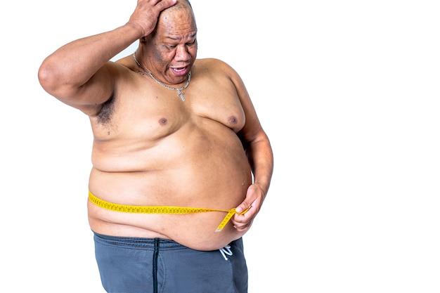 太った黒人ダイエット男は、彼の驚いた腰を巻尺で測定し、彼が政権で体重を減らしたかどうかを確認します。健康と肥満の概念 Premium写真