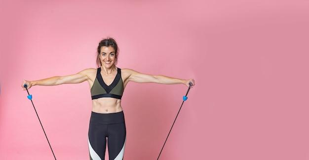 フィットネスライフスタイルトレーニングとゴムバンドでストレッチ体操を行う幸せな若いブルネットの髪の女性 Premium写真