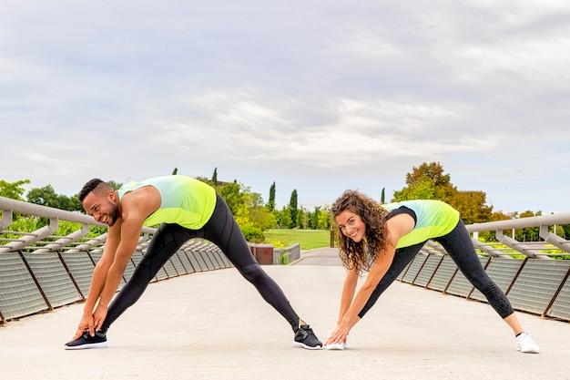 黒人男性と白人女性のカップルは、橋の上の公園で自分の足でストレッチ体操を行い、彼らは足を開いてうずくまっています Premium写真