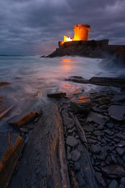 バスク地方のドニバンロヒツネ湾にあるソコアの勇敢な大西洋に囲まれた小さな城。 Premium写真