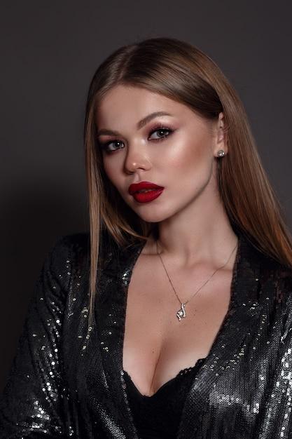 Портрет молодой женщины со светлыми волосами в черном костюме Premium Фотографии
