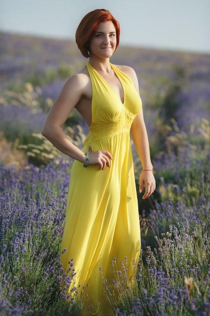 Улыбка красивая брюнетка в сиреневом поле на закате Premium Фотографии