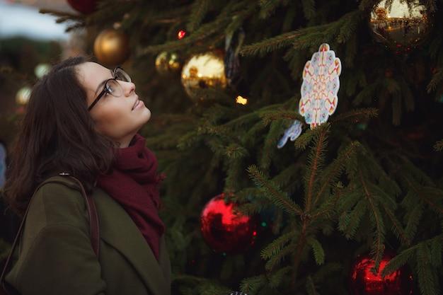 路上で雪の天気を楽しんでうれしそうな幸せな女の子。 Premium写真