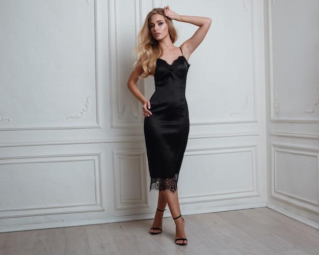 Милая блондинка в шикарном черном платье Premium Фотографии