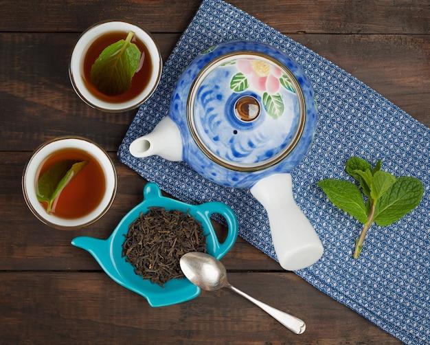 Цельный листовой чай, чайник, две чашки, мята Premium Фотографии