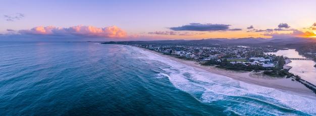 ゴールドコーストの海岸線に沈む夕陽。オーストラリア、クイーンズランド州ゴールドコースト Premium写真
