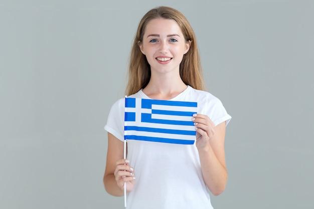 Молодая женщина с флагом греции в руке, изолированных на сером Premium Фотографии