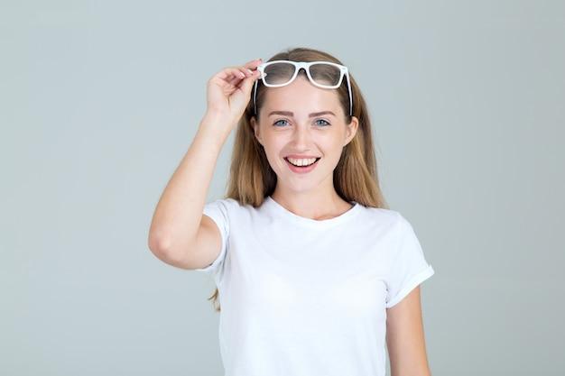 うれしそうな若い女性は彼女の眼鏡を上げた彼女の頭は、灰色の分離 Premium写真