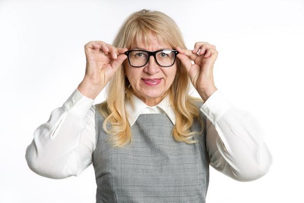 明るい背景に眼鏡の成熟した女性の肖像画。笑顔、ポジティブな感情。 Premium写真