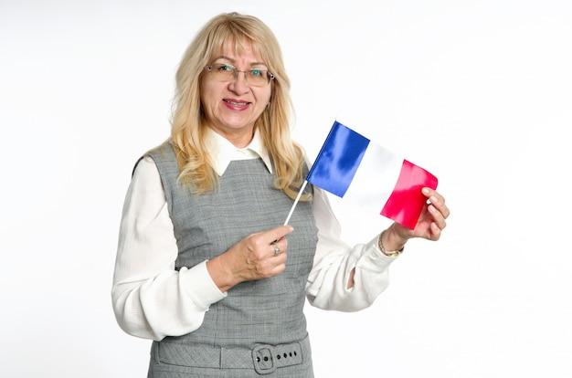 明るい背景にフランスの旗を持つ成熟した女性。 Premium写真