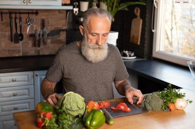 木の板にひげを生やした年配の男性カット野菜木の板にひげを生やした年配の男性カット野菜 Premium写真