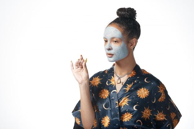 分離された皮膚モデルに粘土美容マスクを持つ面白い容少女 Premium写真