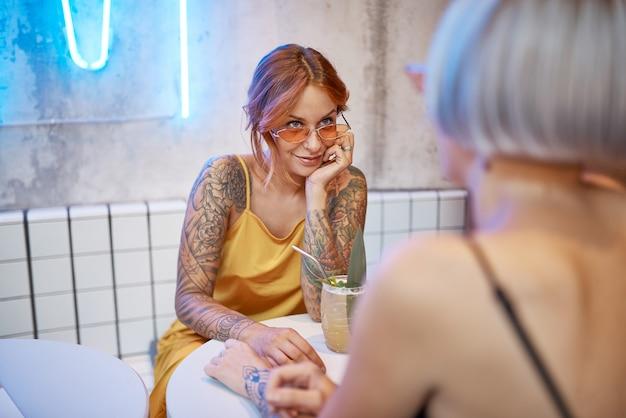 Красивая татуированная рыжая девушка в кафе Premium Фотографии