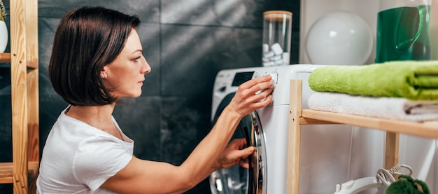 Женщина выбирает программу на стиральной машине Premium Фотографии