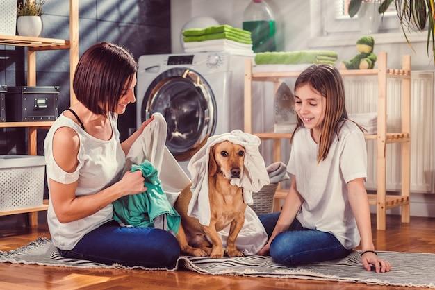 母、娘、犬のランドリールームで楽しんで Premium写真