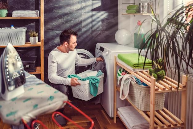 Мужчина кладет одежду в стиральную машину Premium Фотографии