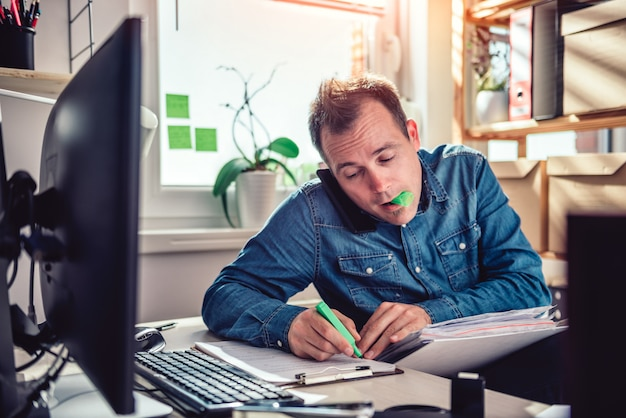 電話で話しているとドキュメントフォルダー内のテキストを強調表示する男 Premium写真
