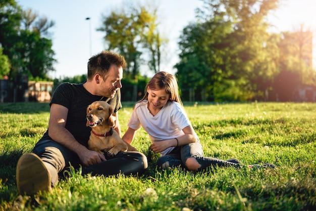 父と娘の犬と一緒に公園でリラックス Premium写真