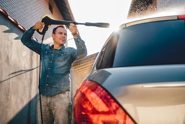 高圧洗浄機で彼の車を洗う人 Premium写真