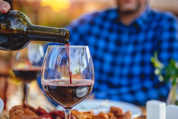 赤ワインを注ぐ男性の写真をクローズアップ Premium写真