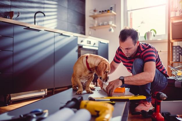 Человек с собакой строит кухонные шкафы Premium Фотографии