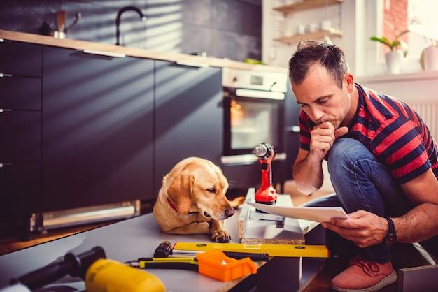 Человек с собакой, проверка чертежей при строительстве кухонных шкафов Premium Фотографии