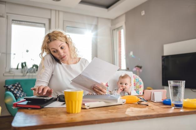 Мать разговаривает по смартфону в домашнем офисе Premium Фотографии