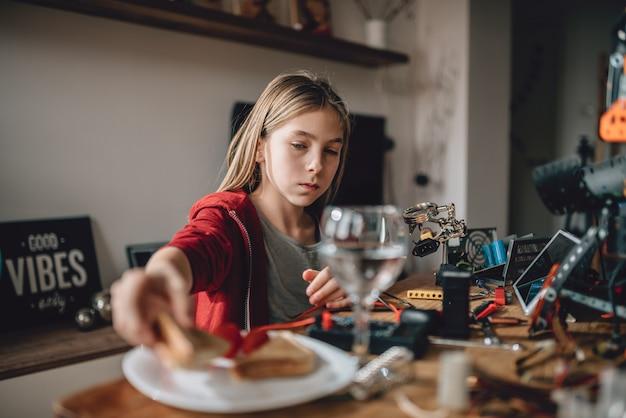 サンドイッチを食べる赤いパーカーを着ている少女 Premium写真